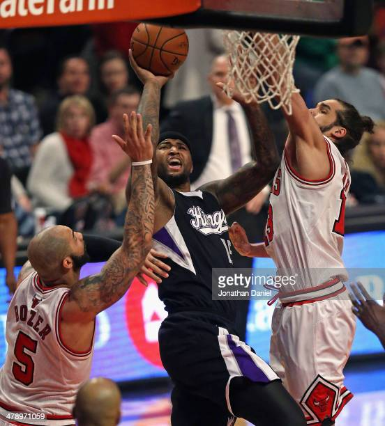 DeMarcus Cousins of the Sacramento Kings shoots between Carlos Boozer and Joakim Noah of the Chicago Bulls at the United Center on March 15 2014 in...