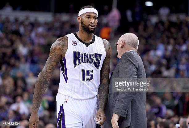 DeMarcus Cousins of the Sacramento Kings walks back to the bench past head coach George Karl after Cousins was called for a technical foul against...
