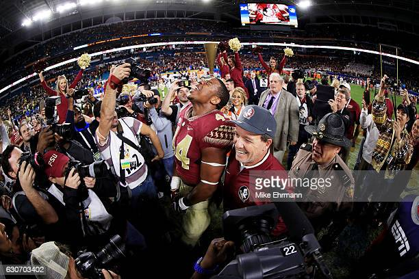 DeMarcus Walker and head coach Jimbo Fisher of the Florida State Seminoles celebrate their 33 to 32 win over the Michigan Wolverines during the...