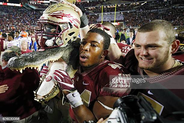 DeMarcus Walker of the Florida State Seminoles carries a gator head wearing his helmet as he celebrates after the game against the Florida Gators at...