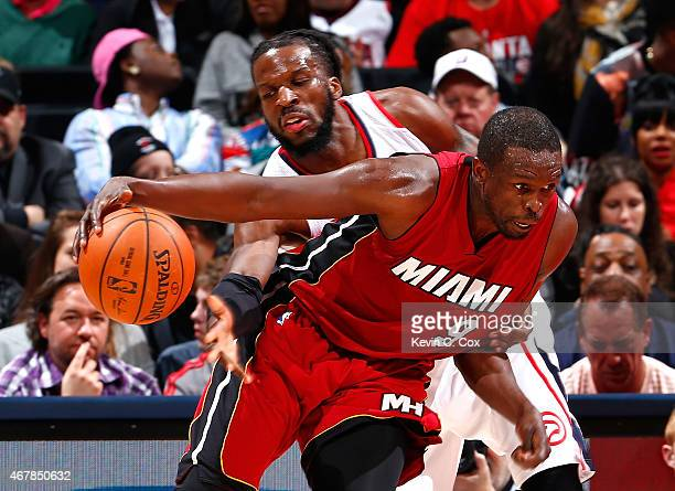 DeMarre Carroll of the Atlanta Hawks reaches for a steal against Luol Deng of the Miami Heat at Philips Arena on March 27 2015 in Atlanta Georgia...