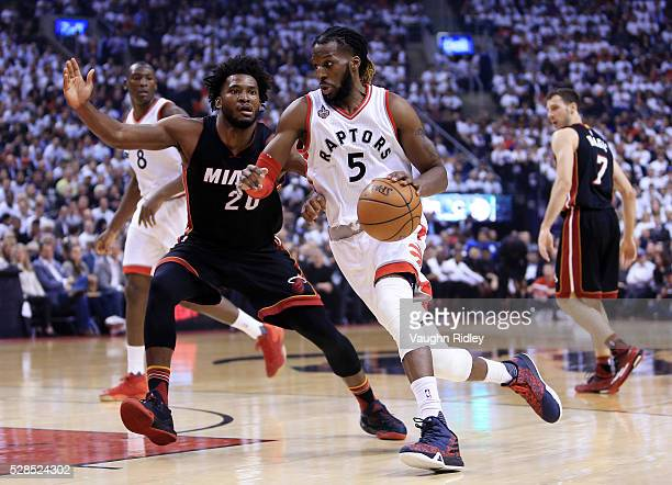 DeMarre Carroll of the Toronto Raptors dribbles the ball as Justice Winslow of the Miami Heat defends in the first half of Game Two of the Eastern...