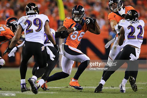 Demaryius Thomas of the Denver Broncos catches a pass in front of Michael Huff of the Baltimore Ravens in the second quarter during the game at...