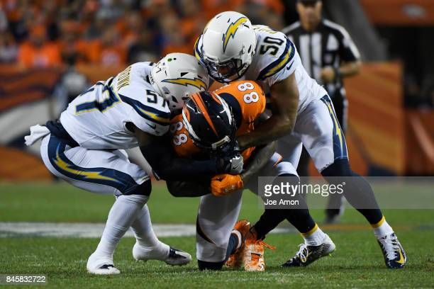 Demaryius Thomas of the Denver Broncos is tackled by Jatavis Brown of the Los Angeles Chargers and Charmeachealle Moore during the first quarter on...
