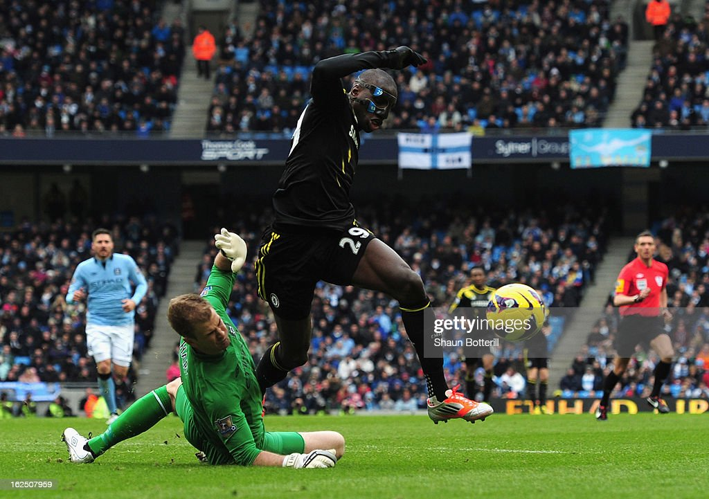 Demba Ba of Chelsea is tackled by Joe Hart of Manchester City for a penalty during the Barclays Premier League match between Manchester City and Chelsea at Etihad Stadium on February 24, 2013 in Manchester, England.