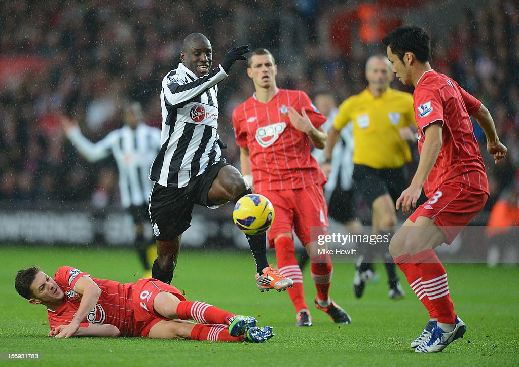 Demba Ba of Newcastle is challenged by Adam Lallana of Southampton during the Barclays Premier League match between Southampton and Newcastle United at St Mary's Stadium on November 25, 2012 in Southampton, England.