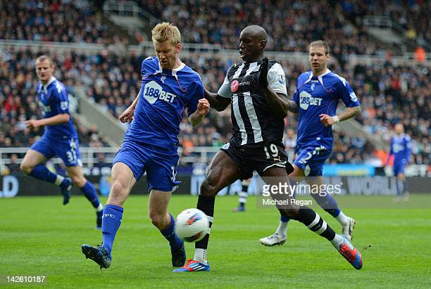 Demba Ba of Newcastle is tackled by Tim Ream of Bolton during the Barclays Premier League match between Newcastle United and Bolton Wanderers at the...