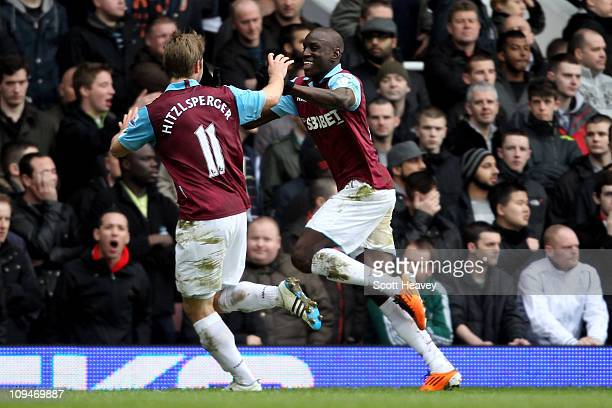 Demba Ba of West Ham celebrates with teammate Thomas Hitzlsperger as he scores the second goal during the Barclays Premier League match between West...