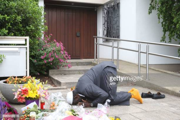 Dembo Kvubally from Gambia prays next to flowers and candles placed in front of the house of former German Chancellor Helmut Kohl in Oggersheim near...