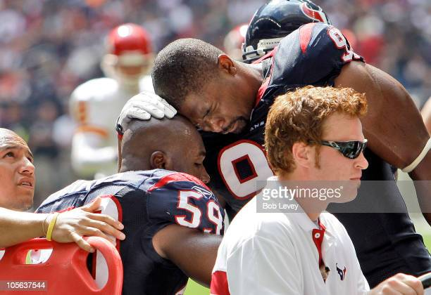 DeMeco Ryans of the Houston Texans is comforted by Amobi Akoye as he is carted off the field at Reliant Stadium on October 17 2010 in Houston Texas