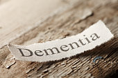 "The word 'Dementia"" on a torn piece of paper that rests on an old weathered piece of wood.  The old paint is flaking off of the wood surface to help convey the feeling of age."