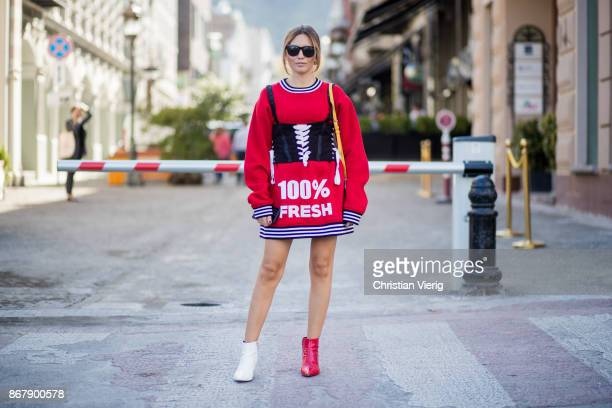 Demet Kamis wearing red sweater worn as a dress with the print 100 percent fresh two tone red white ankle boots corset is seen during Tbilisi Fashion...