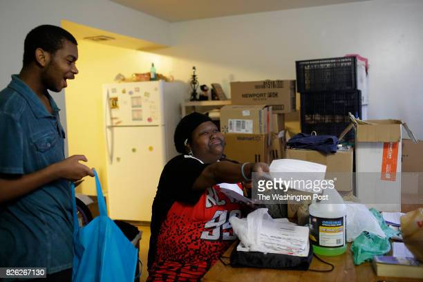 Demetra Turner reacts found her move out letter she received to vacate her apartment as her son Jeremiah Kinley looks on at the West Calumet Housing...