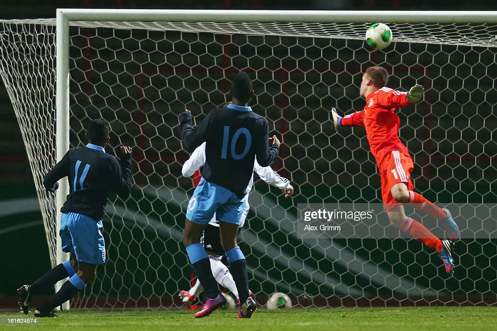 Demetri Mitchell (L) of England scores his team's second goal against goalkeeper Patrick Bade of Germany during the U16 international friendly match between Germany and England at Suedstadion on February 13, 2013 in Cologne, Germany.