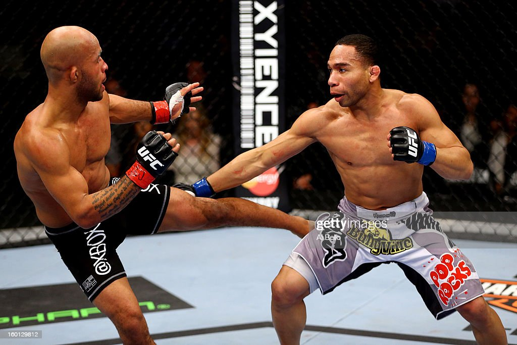 Demetrious Johnson (L) kicks John Dodson (R) during thier Flyweight Championship Bout part of UFC on FOX at United Center on January 26, 2013 in Chicago, Illinois.