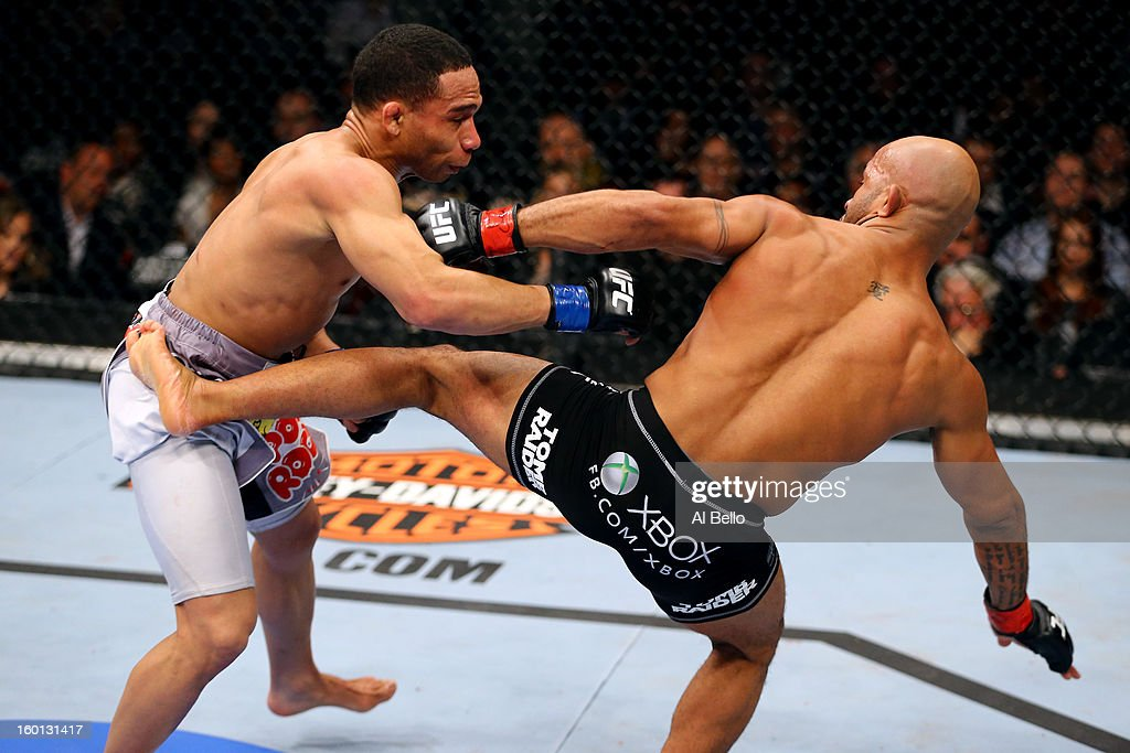 Demetrious Johnson (R) kicks John Dodson (L) during thier Flyweight Championship Bout part of UFC on FOX at United Center on January 26, 2013 in Chicago, Illinois.