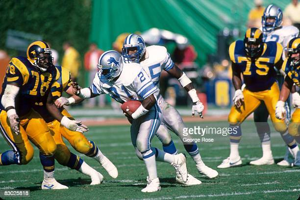 Demetrious Johnson of the Detroit Lions runs the ball past Jackie Slater of the Los Angeles Rams during a game at Anaheim Stadium on October 19 1986...