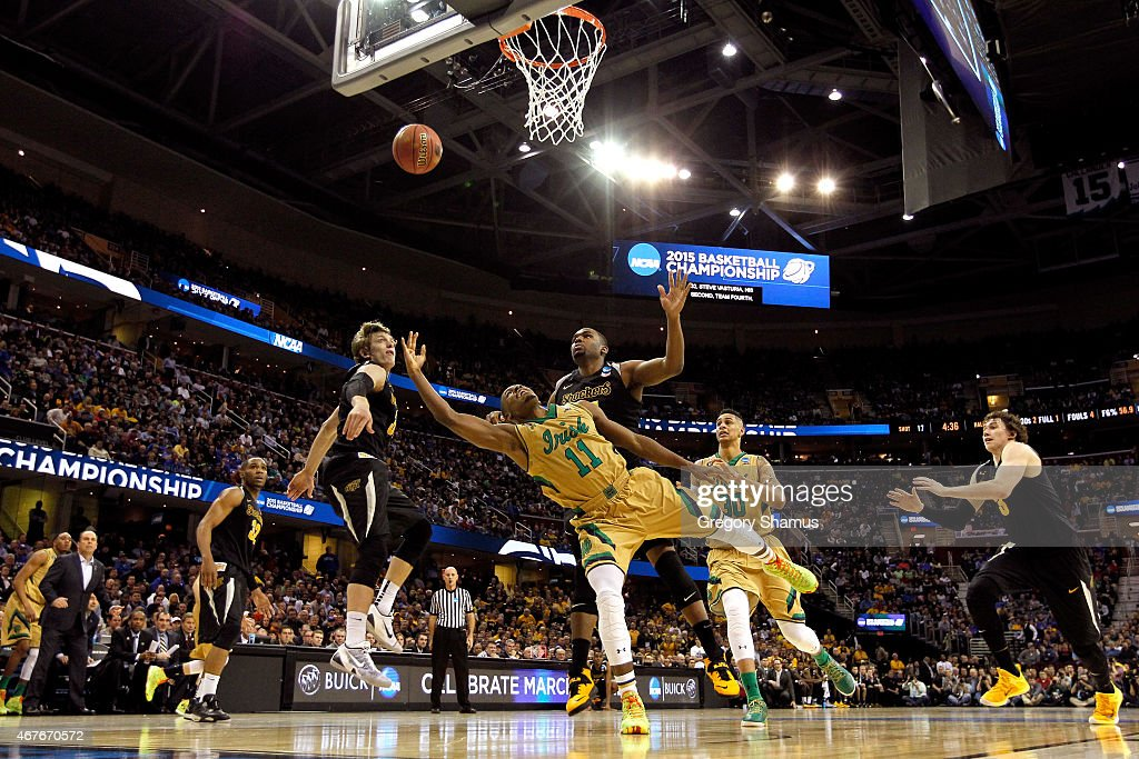 Demetrius Jackson #11 of the Notre Dame Fighting Irish drives to the basket against Ron Baker #31 and Shaquille Morris #24 of the Wichita State Shockers in the second half during the Midwest Regional semifinal of the 2015 NCAA Men's Basketball Tournament at Quicken Loans Arena on March 26, 2015 in Cleveland, Ohio.