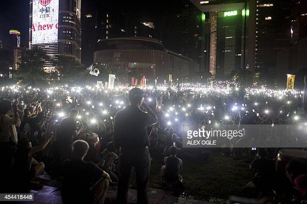 Democracy activist Chan Kin Man looks out at protesters waving their mobile phones and other electronic devices as they take part in a prodemocracy...