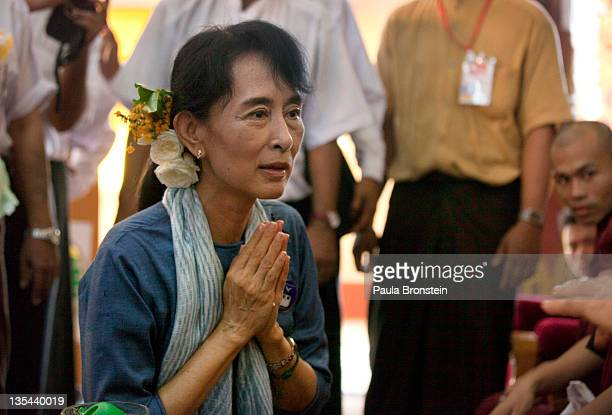 Democracy leader Aung San Suu Kyi greets a monk during 20th anniversary ceremonies to honor her winning the Nobel Peace prize December 10 2011 in...