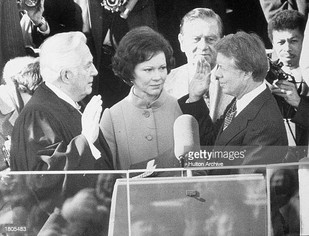 Democrat Jimmy Carter is sworn in by chief justice Earl Burger as the 39th president of the United States while first lady Rosalynn looks on...
