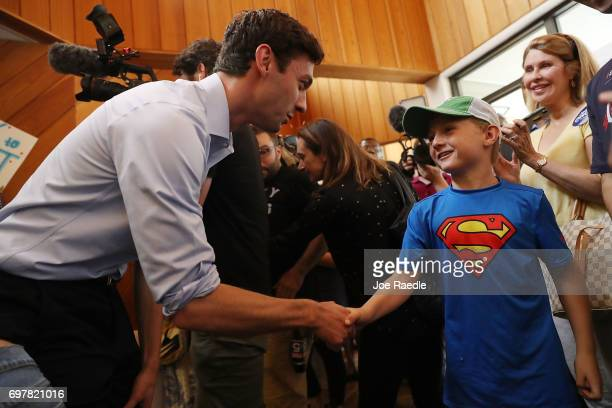 Democratic candidate Jon Ossoff shakes hands with Grayden Auchincloss during a visit to a campaign office to thank volunteers and supporters as he...