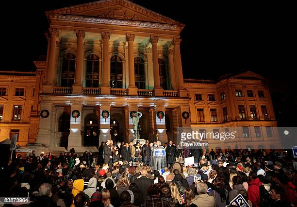 Democratic challenger Jim Martin talks with supporters as he campaigns in front of the State Capitol on December 1 2008 in Atlanta Georgia Martin is...