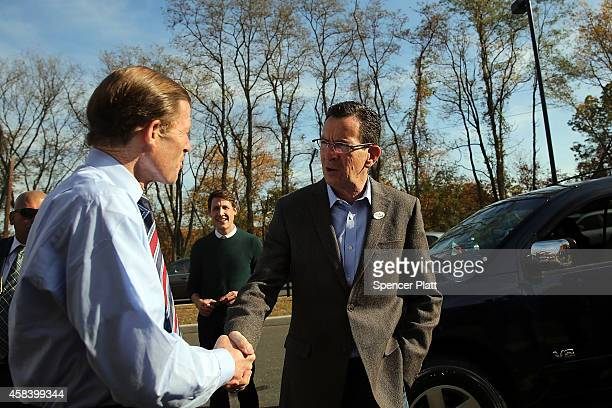 Democratic Connecticut Governor Dan Malloy speaks with Sen Richard Blumenthal at a polling station on November 4 2014 in Bridgeport Connecticut...