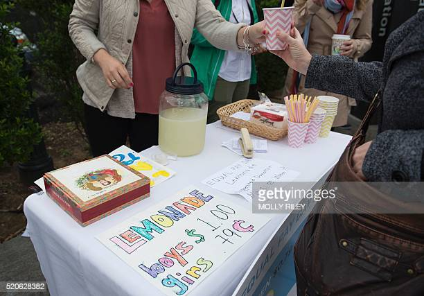Democratic National Committee women host an Equal Pay Day event with a lemonade stand 'where women pay 79 cents per cup and men pay $1 per cup to...