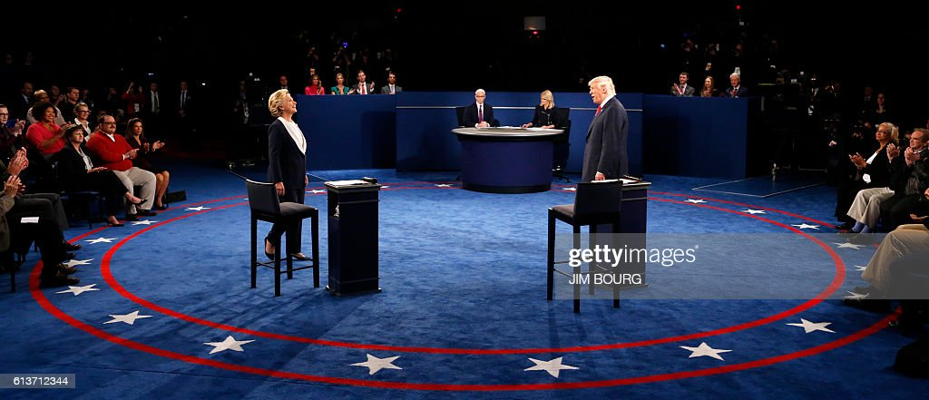 TOPSHOT - Democratic nominee Hillary Clinton (L) and Republican nominee Donald Trump arrive on stage during the second presidential debate at Washington University in St. Louis, Missouri on October 9, 2016. / AFP / POOL / JIM