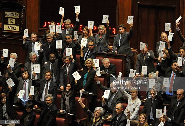 Democratic party deputies protest by holding Consitution books after a final vote on April 13 2011 in the Rome's Montecitorio palace during a debate...
