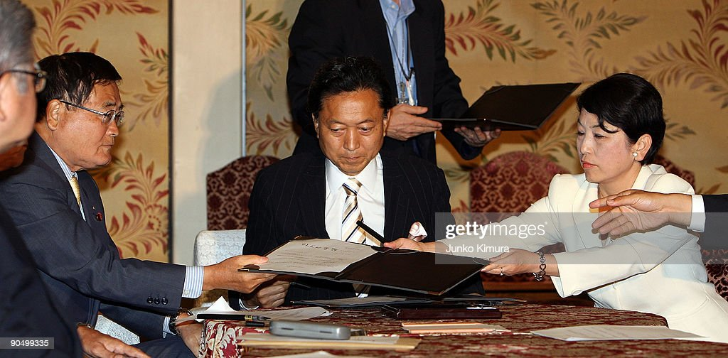 Democratic Party of Japan (DPJ) president and incoming Prime Minister Yukio Hatoyama (C), Social Democratic Party leader Mizuho Fukushima (R) and The People's New Party Shizuka Kamei (L) exchange the documents as they sign during the leaders meeting at the Diet building on September 9, 2009 in Tokyo, Japan. DPJ secured 308 seats out of 480 in the lower house election but still need the coalition with these two parties to keep control in the upper house.
