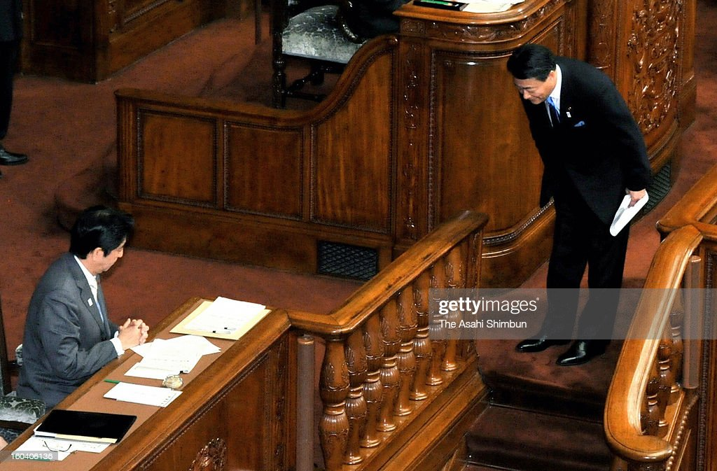 Democratic Party of Japan president Banri Kaieda bows to Prime Minister Shinzo Abe on the way back to his seat after the party representatives' questioning at the lower house on January 30, 2013 in Tokyo, Japan.