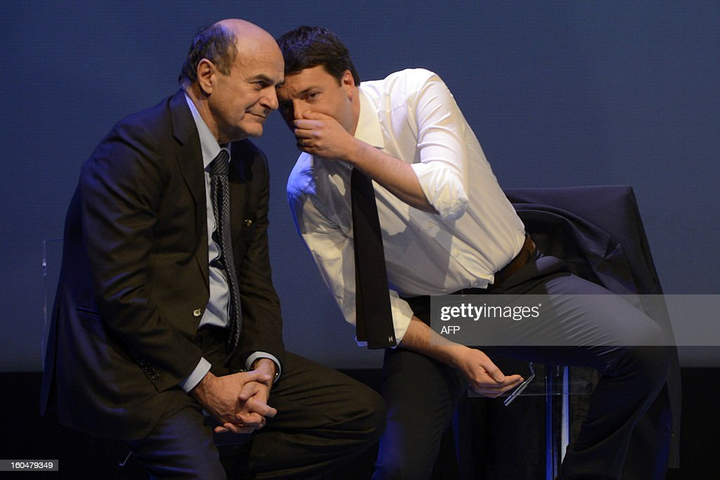 Democratic Party (PD) secretary general Pierluigi Bersani (L) and Florence's mayor Matteo Renzi chat on stage during an electoral rally on February 1, 2013 in Florence. Italians take to the polls on February 24-25. AFP PHOTO / ANDREAS SOLARO