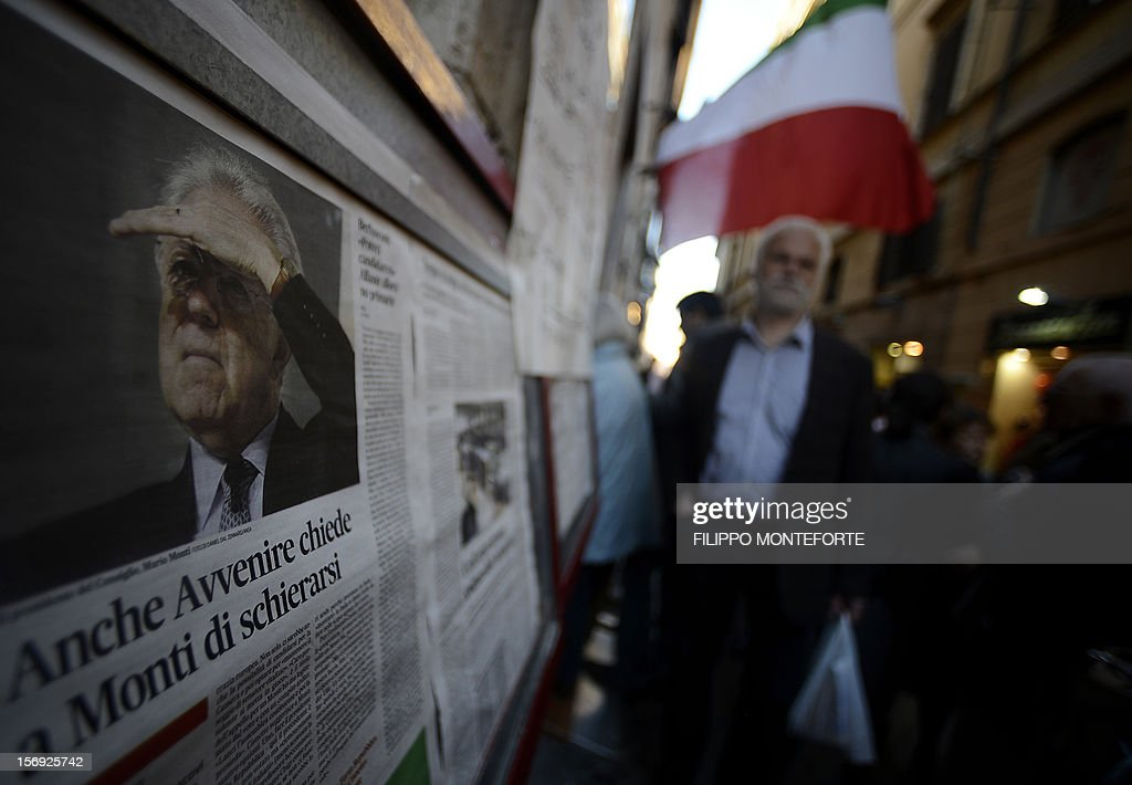 Democratic Party (PD) supporters queue in front of a party polling station, where a newpsaper displays a picture of Italain Prime Minister Mario Monti, to choose between five candidates in the primary election on November 25, 2012 in Rome. Centre-left voters in recession-hit Italy went to the polls on Sunday to choose the Democratic Party candidate who will run for prime minister in an election early next year that it is widely expected to win.