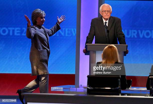 Democratic president candidate Bernie Sanders waits as Hillary Clinton walks on stage at Saint Anselm College December 19 2015 in Manchester New...