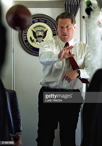 Democratic presidential candidate and US Vice President Al Gore throws a football to a member of his staff aboard his airplane Air Force Two before...