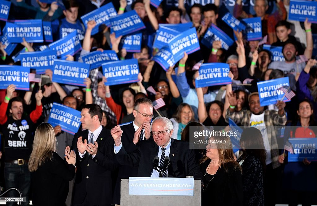 US Democratic presidential candidate Bernie Sanders (C) celebrates his victory during the primary night rally in Concord, New Hampshire, on February 9, 2016. Self-described democratic socialist Bernie Sanders and political novice Donald Trump won New Hampshire's presidential primaries Tuesday, US media projected, turning the American political establishment on its head early in the long nominations battle. / AFP / JEWEL SAMAD