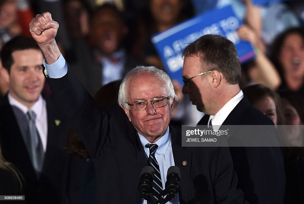 US Democratic presidential candidate Bernie Sanders celebrates his victory during the primary night rally in Concord, New Hampshire, on February 9, 2016. Self-described democratic socialist Bernie Sanders and political novice Donald Trump won New Hampshire's presidential primaries Tuesday, US media projected, turning the American political establishment on its head early in the long nominations battle. / AFP / Jewel Samad