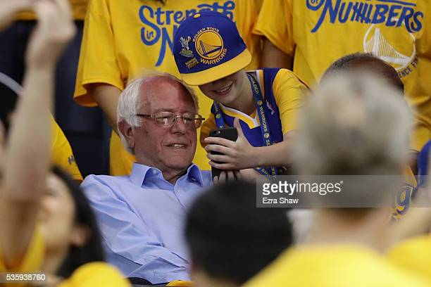 Democratic presidential candidate Bernie Sanders takes a photo with a fan at Game Seven of the Western Conference Finals between the Golden State...