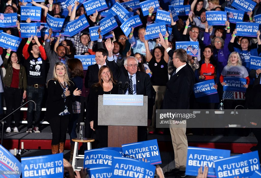 US Democratic presidential candidate Bernie Sanders (C) waves during the primary night rally in Concord, New Hampshire, on February 9, 2016. Self-described democratic socialist Bernie Sanders and political novice Donald Trump won New Hampshire's presidential primaries Tuesday, US media projected, turning the American political establishment on its head early in the long nominations battle. / AFP / JEWEL SAMAD