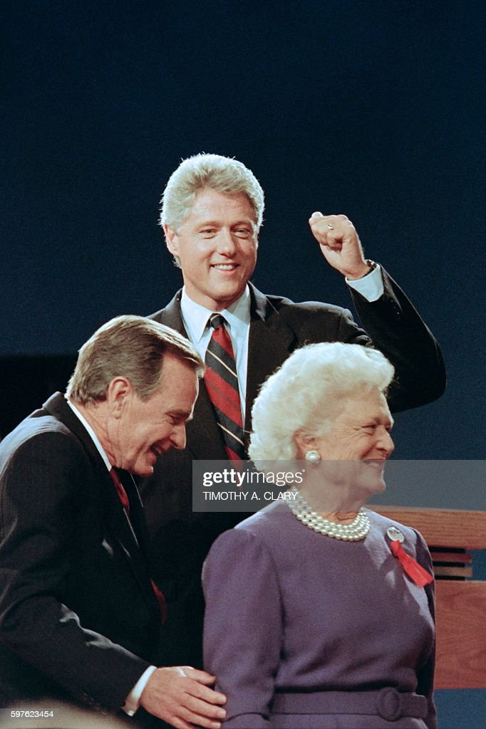 Democratic presidential candidate Bill Clinton gives a thumb up to his supporters as US President George Bush and his wife Barbara exit the stage on...