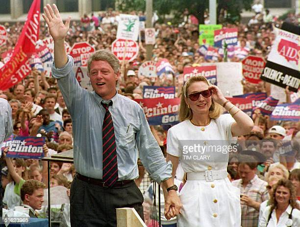 Democratic presidential candidate Bill Clinton waves to supporters as he holds the hand of his wife Hillary 22 July 1992 after speaking at a rally St...