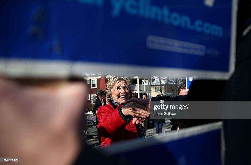 Democratic presidential candidate former Secretary of State Hillary Clinton shakes hands with supporters as she knocks on doors to greet voters on February 6, 2016 in Manchester, New Hampshire. With less than one week to go before the New Hampshire primaries, Hillary Clinton continues to campaign throughout the state.