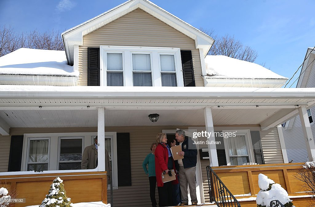 Democratic presidential candidate former Secretary of State Hillary Clinton (L) walks with New Hampshire state senator Lou D'Allesandro leave a home as they knock on doors to greet voters on February 6, 2016 in Manchester, New Hampshire. With less than one week to go before the New Hampshire primaries, Hillary Clinton continues to campaign throughout the state.