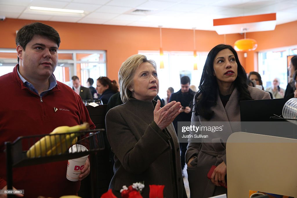 Democratic presidential candidate former Secretary of State Hillary Clinton (C) prepares to order food at a Dunkin Donuts with New Hampshire state campaign director Mike Vlacich (L) and aide Huma Abedin (R) on February 7, 2016 in Manchester, New Hampshire. With less than one week to go before the New Hampshire primaries, Hillary Clinton continues to campaign throughout the state.