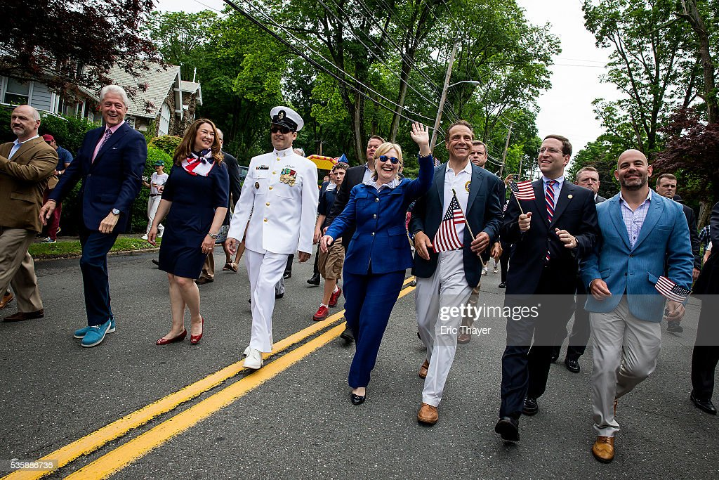 Democratic presidential candidate former Secretary of State Hillary Clinton, former President Bill Clinton and New York Governor Andrew M. Cuomo walk in the Memorial Day parade May 30, 2016 in Chappaqua, New York.