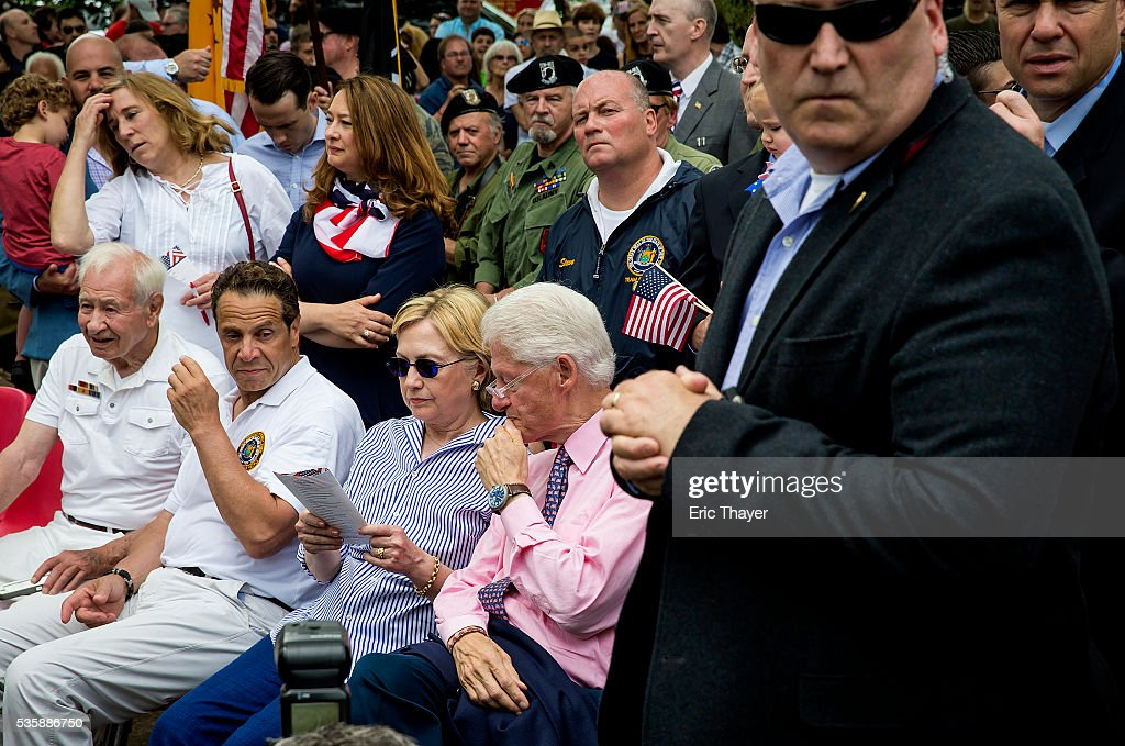Democratic presidential candidate former Secretary of State Hillary Clinton, former President Bill Clinton and New York Governor Andrew M. Cuomo attend a ceremony after the Memorial Day parade May 30, 2016 in Chappaqua, New York.