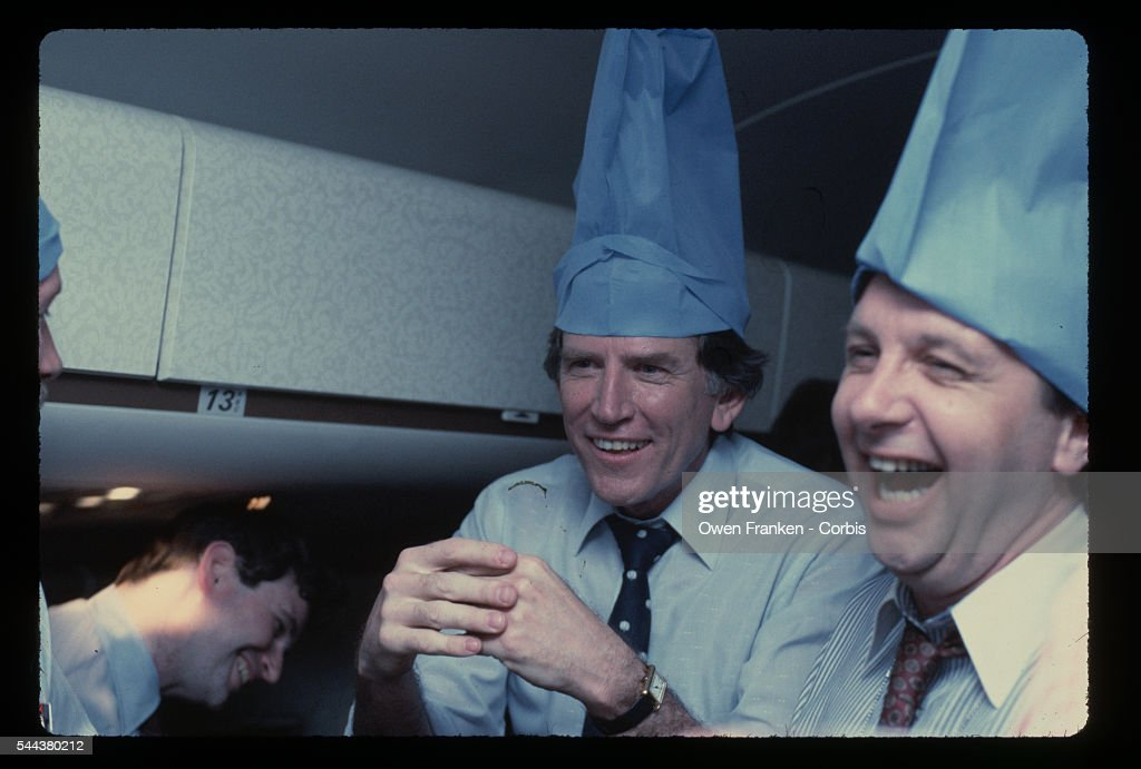 Democratic presidential candidate Gary Hart wears a blue pillowcase on his head and jokes with journalists aboard his campaign airplane during the...