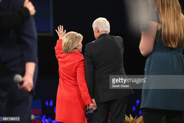 Democratic presidential candidate Hillary Clinton and her husband former president Bill Clinton hold hands as they wave to guests at the end of the...